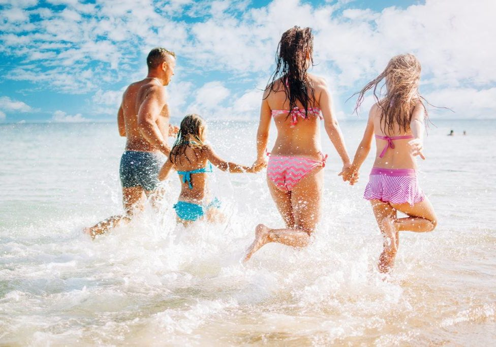 Happy family having fun on the beach. They with holding hands running and splashing in the sea.