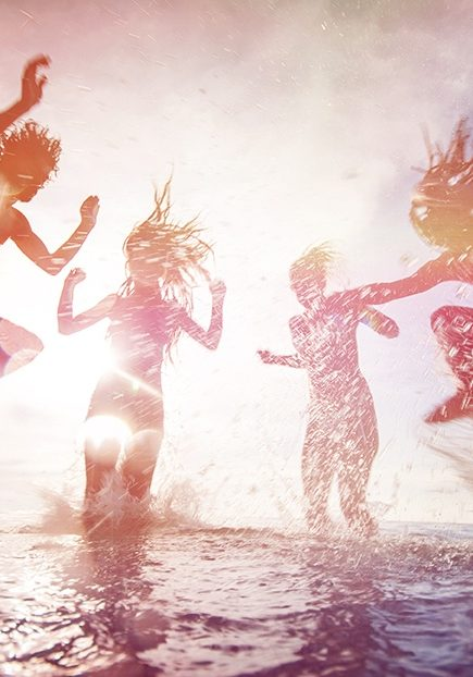 Silhouettes of happy young people jumping in sea at the beach on summer sunset